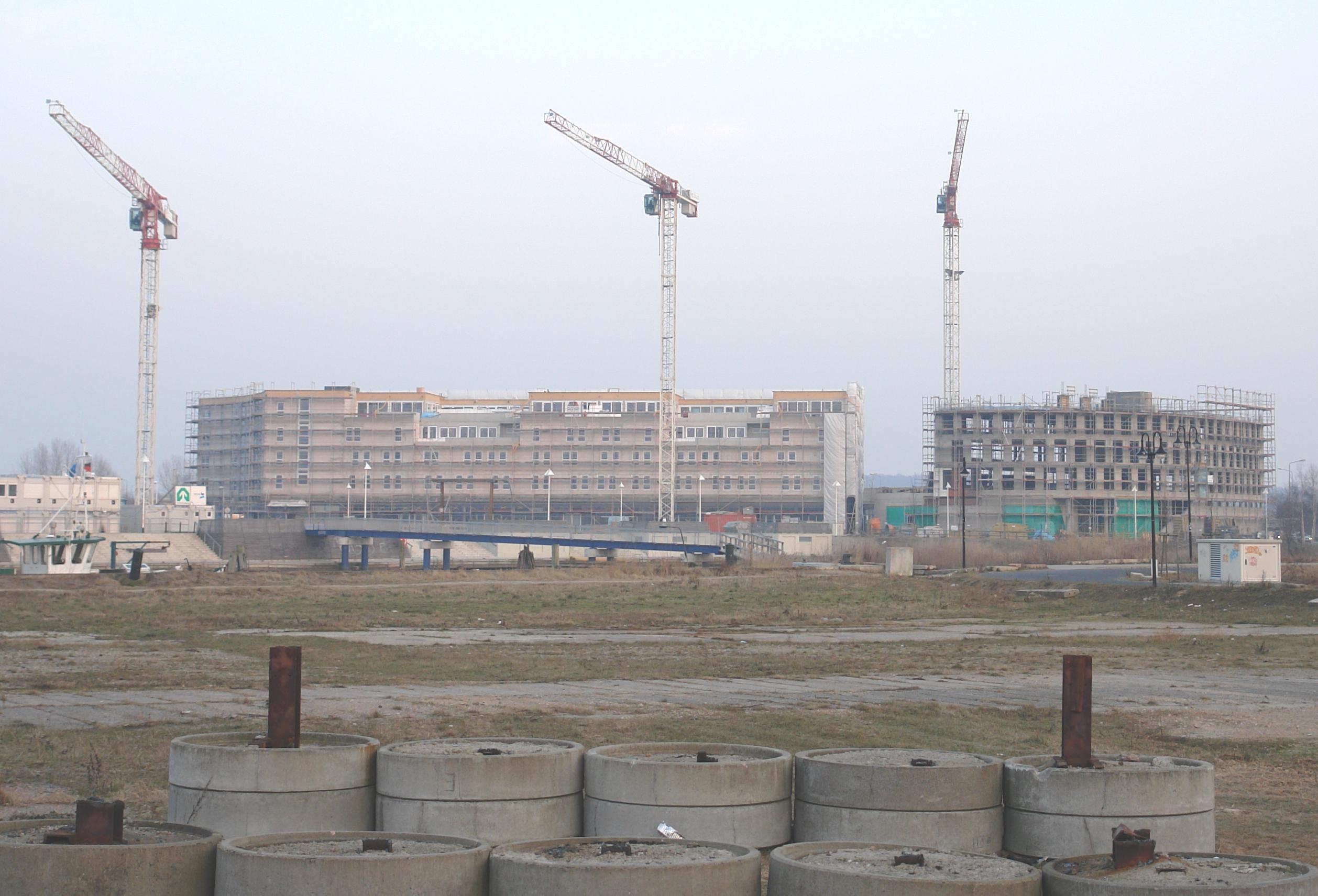 Das Foto zeigt zwei große Gebäude, bei denen drei Kräne stehen.