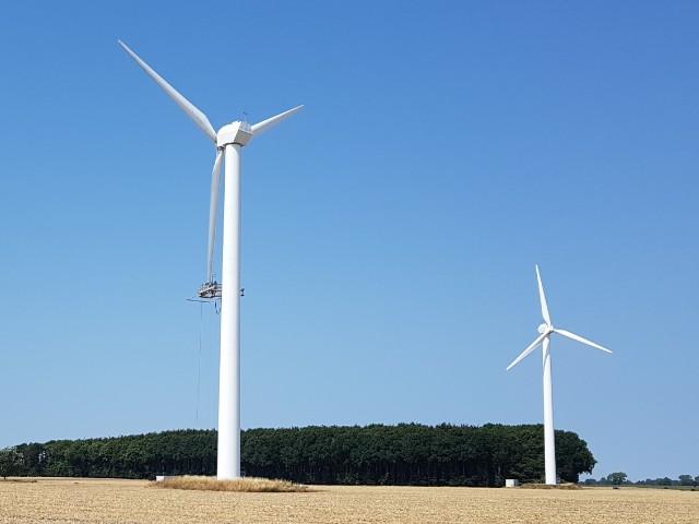 Zu erkennen sind zwei Windenergieanlagen, an einer hängt an einem nach unten gerichteten Rotorblatt ein Mannkorb für Reparaturarbeiten.