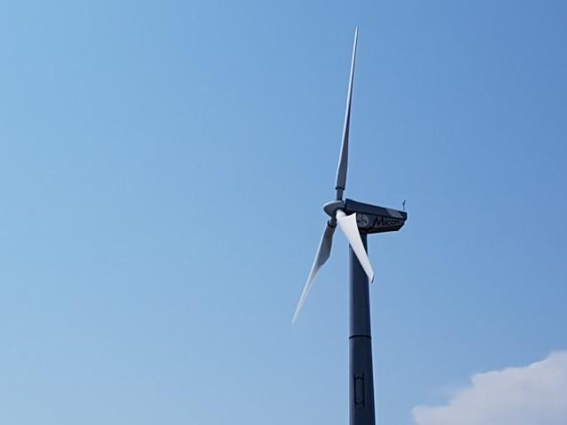 Das Foto zeigt eine Windkraftanlage vor blauem Himmel, unten rechts ist ein wenig Bewölkung zu sehen.