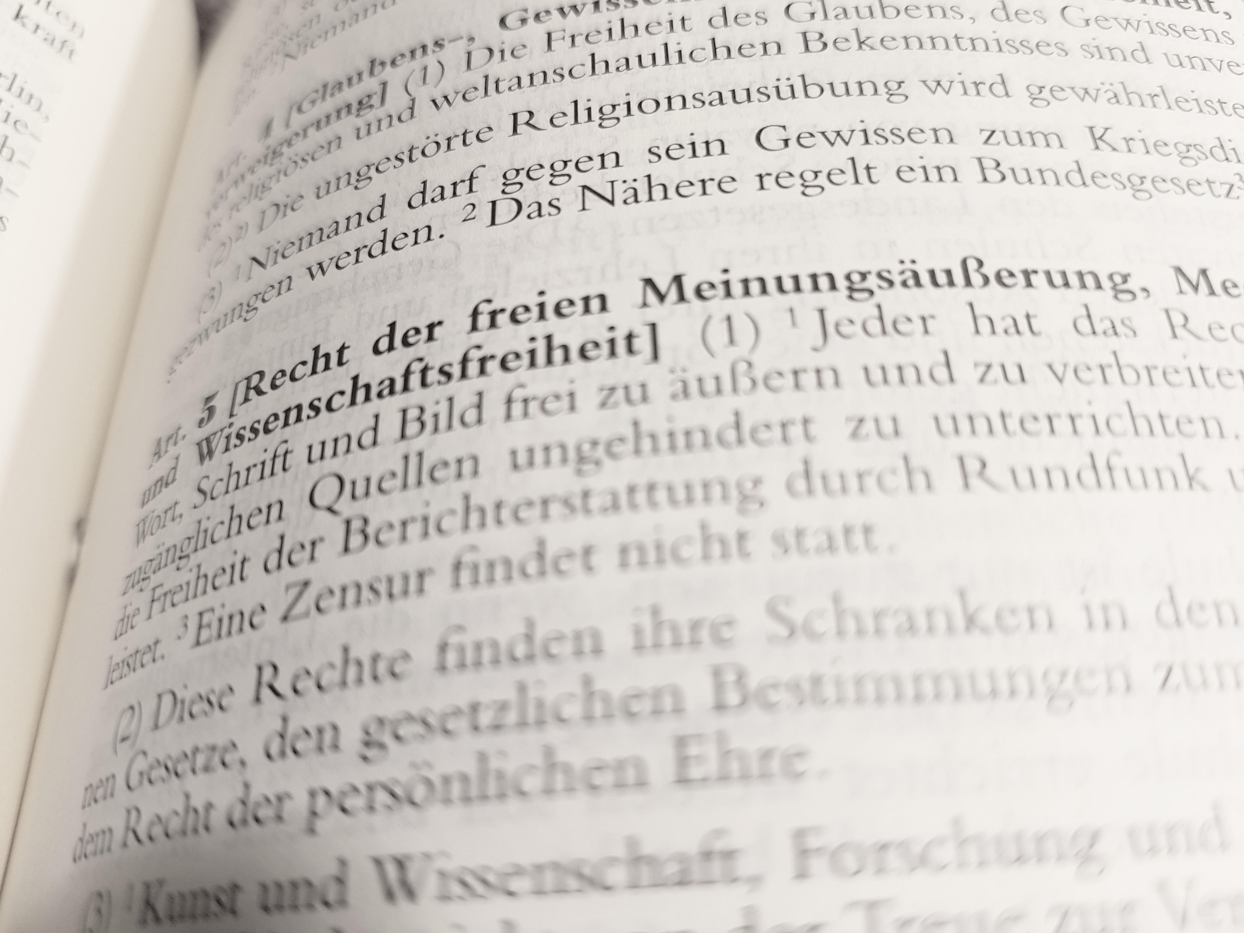 Das Foto zeigt den Blick in das Grundgesetz, wo Artikel 5 Meinungsfreiheit zu sehen ist.