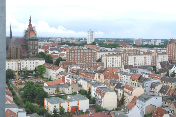 Das Foto zeigt Häuser der Stadt Rostock, darunter eine Kirche und mehrere Altbauhäuser.
