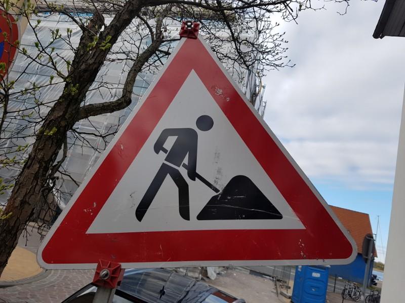 Auf dem Foto ist ein dreieckiges rot umrandetes Baustellenschild zu sehen, welches einen stilisierten Bauarbeiter, schwarz auf weißem Grund, zeigt, welcher mit einem Spaten in einem Haufen schaufelt.