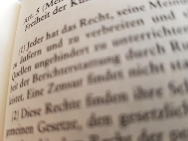 Das Foto zeigt den Blick in ein Gesetzbuch, aufgeschlagen ist es beim Grundgesetz, Artikel 5 Meinungsfreiheit.