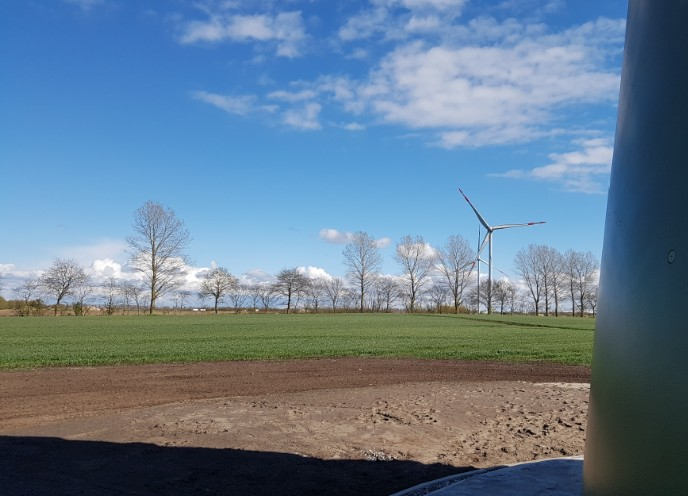 Das Foto zeigt eine Windenergieanlage in der Landschaft. Vorn rechts ist ein Windenergieanlagen Turm zu sehen sowie dessen Schatten.