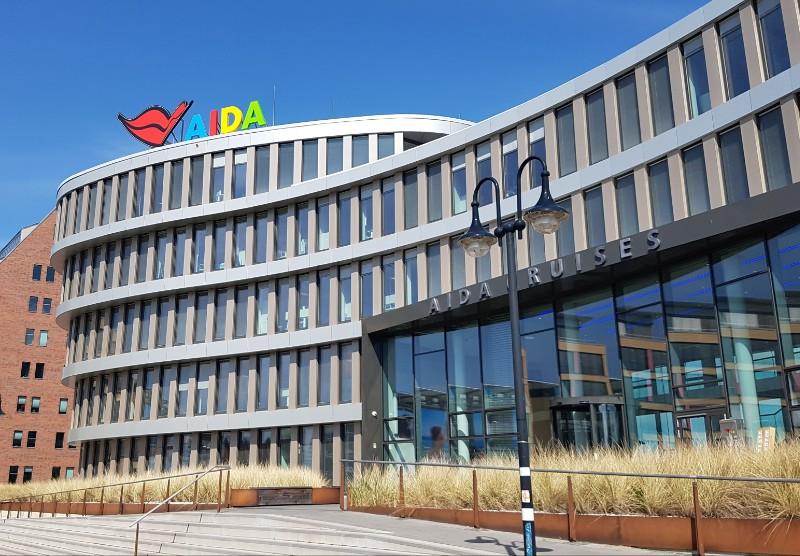 Das Foto zeigt ein Gebäude, auf dem oben das Wort AIDA angebracht ist sowie ein roter Kussmund.
