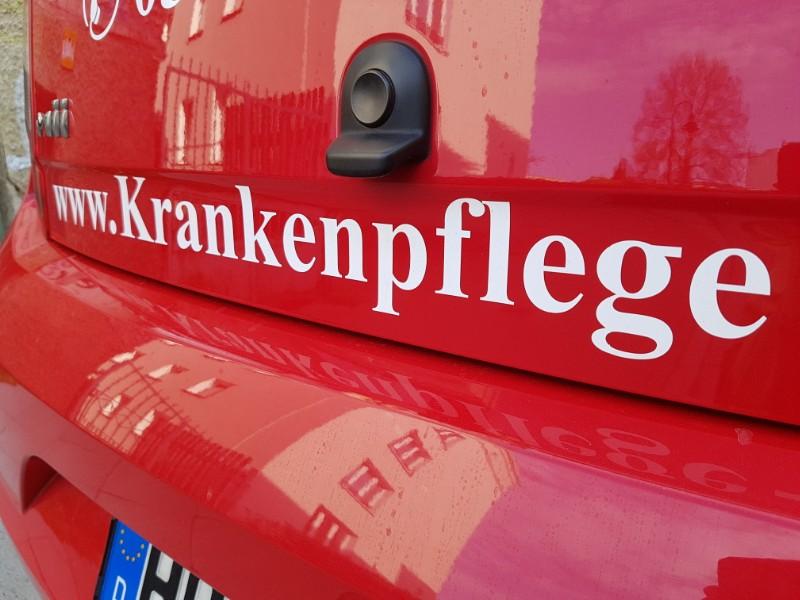 Das Foto zeigt ein rotes Auto, bei welchem auf der Heckklappe das Wort Krankenpflege zu lesen ist.