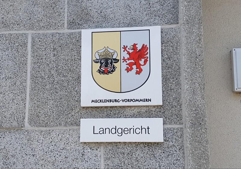 Das Foto zeigt das Landeswappen des Landes Mecklenburg-Vorpommern, darunter ein Schild mit der Aufschrift Landgericht.