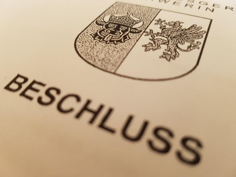 Das Foto zeigt das Deckblatt eines Beschlusses des Verwaltungsgerichts, zu erkennen ist das Landeswappen des Bundeslandes Mecklenburg-Vorpommern und darunter das Wort Beschluss.