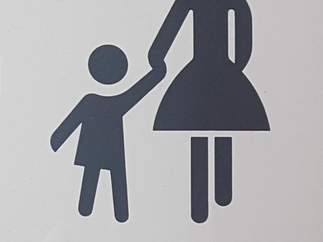 Schwarz auf weißem Grund ist eine stilisierte Frau zusammen mit einem Kind zu erkennen, welches die Frau an der Hand hält.