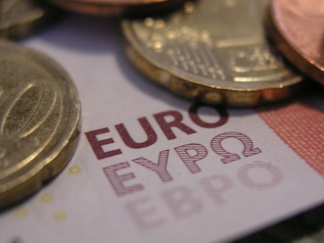 Das Foto zeigt Geldmünzen, die auf einem 10 Euro Schein, welcher nur zum Teil zu erkennen ist, liegen.
