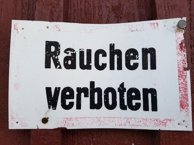 Das Foto zeigt ein Rauchen verboten Schild. Die Schrift ist schwarz auf weißem Grund, das lädierte Schild ist rot umrandet.