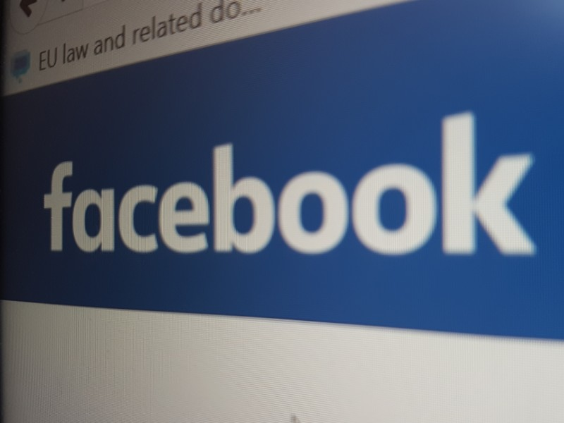 Auf dem Foto ist, vom Bildschirm abfotografiert, der Schriftzug Facebook zu erkennen.
