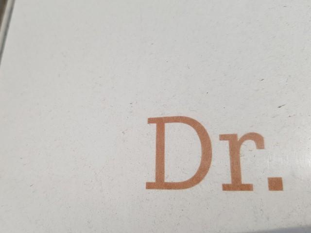 Das Foto zeigt den Ausschnitt eines Schildes, auf dem die beiden Buchstaben Dr. als Abkürzung für Doktor zu sehen sind.