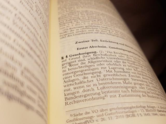 Das Foto zeigt den Blick in ein aufgeschlagenes Gesetzbuch, zu sehen ist Paragraph 4 Genehmigung.