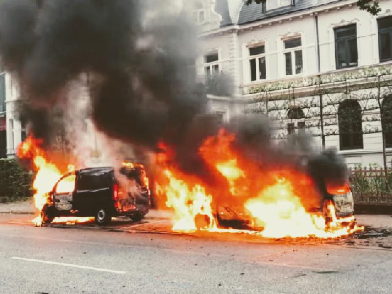 Das Foto zeigt brennende Autos, die vor einer Häuserfassade stehen.