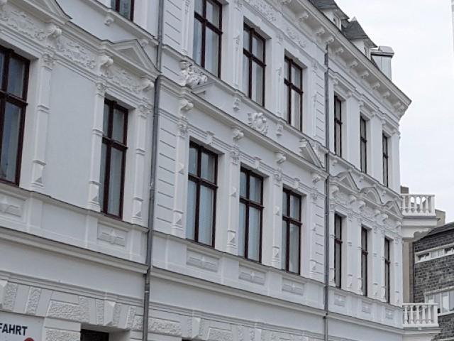 Das Foto zeigt die Fassade eines Gebäudes mit einigen Fenstern und Verzierungen.