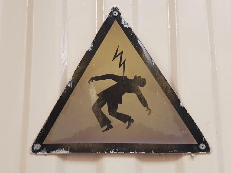 Das Foto zeigt das dreieckige schwarz umrandete Warnschild vor Stromschlag, auf dem ein Mann zu sehen ist, welcher theatralisch nach hinten gebeugt steht und der an der Brust von einem von oben kommenden Blitz getroffen wird.