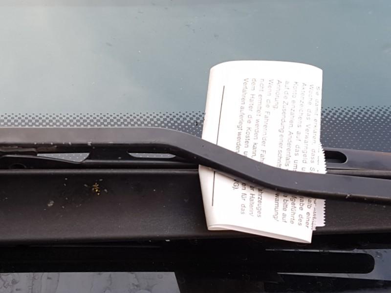 Das Foto zeigt einen Strafzettel, der unter den Scheibenwischer eines Fahrzeugs geklemmt ist.
