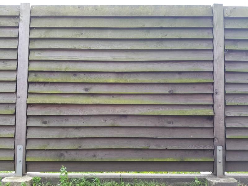 Das Foto zeigt einen Holzzaun mit horizontal angebrachten Latten.