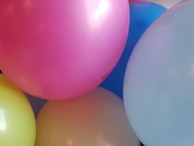 Das Foto zeigt einige Luftballons mit unterschiedlichen Farben, unter anderem pink, blau, hellblau, gelb.