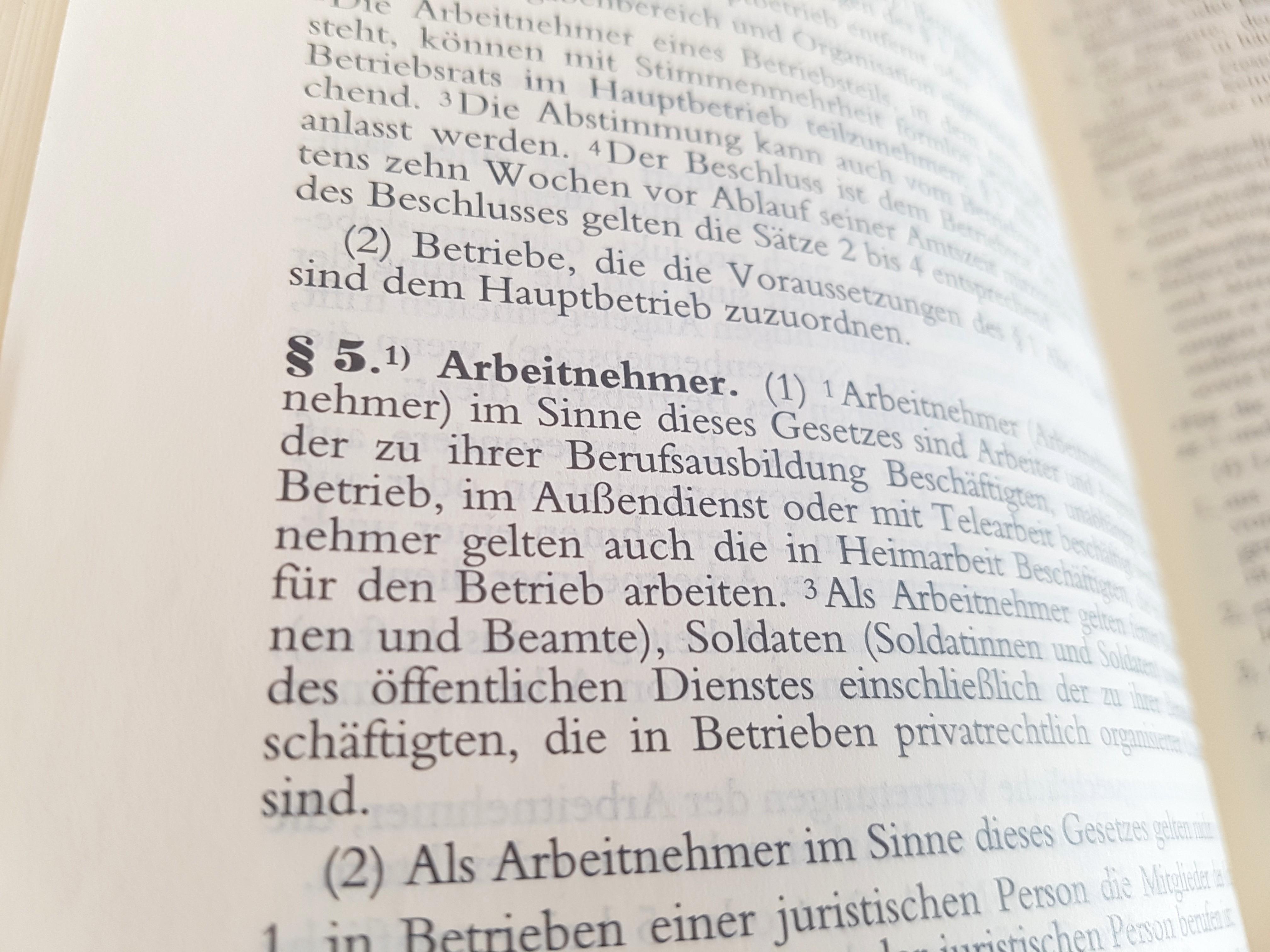 Das Foto zeigt den Blick in ein Gesetzbuch, in dem Paragraph 5 Arbeitnehmer zu erkennen ist.