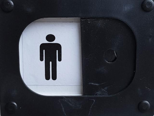 Das Foto zeigt einen symbolisierten Mann schwarz auf weißem Grund und eingefasst in einen schwarzen Rahmen aus Kunststoff.