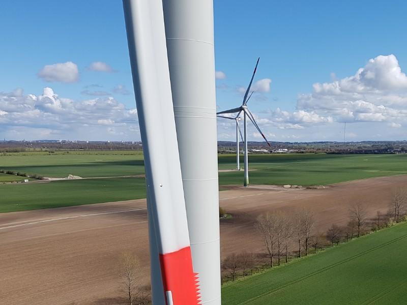 Das Foto zeigt mehrere Windenergieanlagen in der Landschaft. Es sind landwirtschaftliche Flächen zu erkennen, im Hintergrund blauer Himmel mit einigen Wolken.