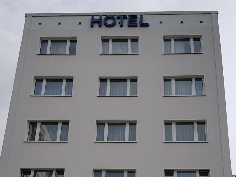 Das Foto zeigt die Fassade eines Hotels mit mehreren Fenstern und oben dem angebrachten Schriftzug Hotel.