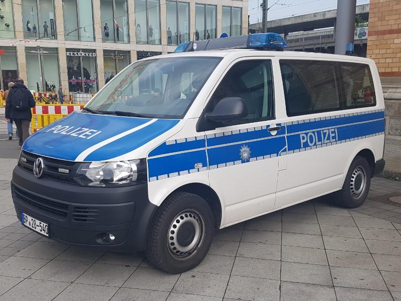Das Foto zeigt ein Polizeiauto, VW Bus T4, schräg von vorne fotografiert.