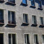 Das Foto zeigt die Fassade eines Gebäudes, mit grauem Putz und offenkundig sanierungsbedürftig.
