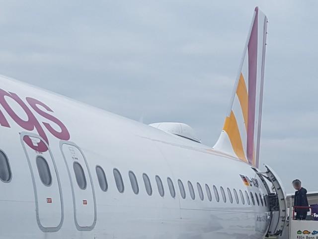 Das Foto zeigt ein Flugzeug mit angestellter Gangway, auf die gerade Passagiere gehen.