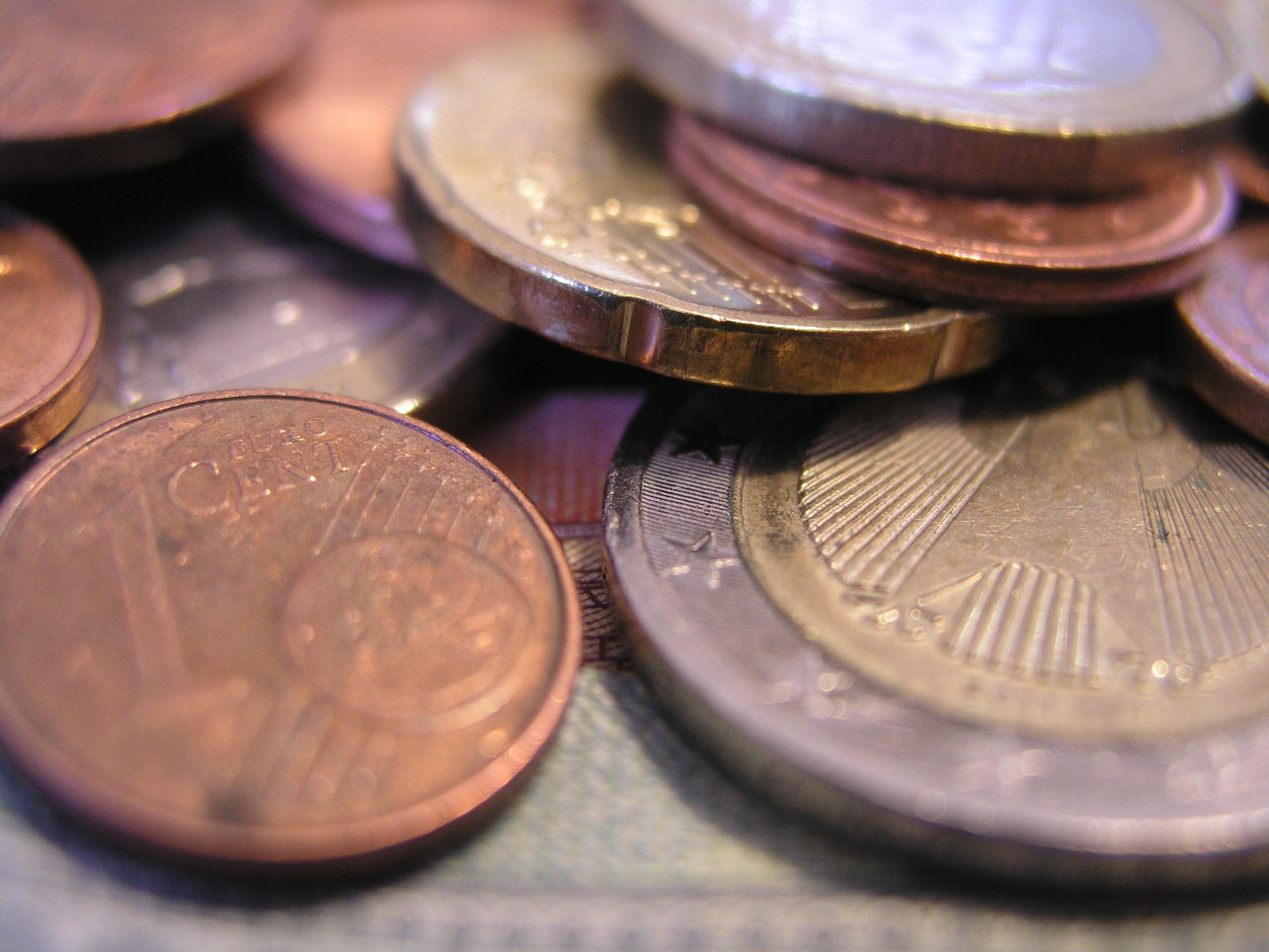 Das Foto zeigt zahlreiche Geldmünzen, die auf einem Geldschein liegen.