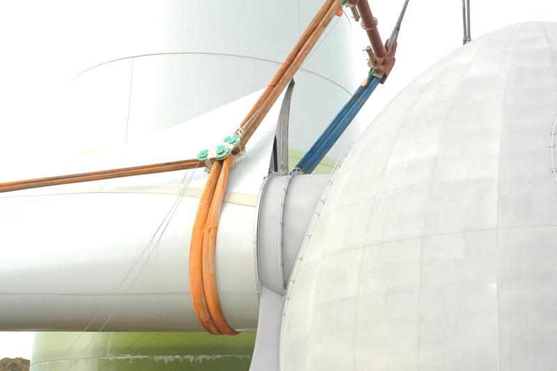 Das Foto zeigt eine Gondel einer Windenergieanlage, der an einem Kranseil befestigt ist, im Hintergrund ist der Turm einer Windenergieanlage zu sehen.