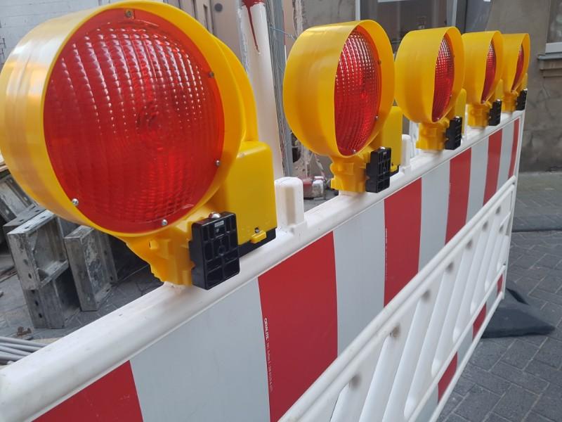 Das Foto zeigt eine Straßenabsperrung, aus Kunststoff rot weiß mit oben aufgesetzten gelb eingefassten roten Leuchten.