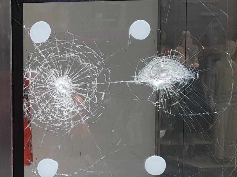 Das Foto zeigt ein Schaufenster, welches zwei durch Gewalteinwirkung hervorgerufene Beschädigungen aufweist, von diesen gehen zahlreiche Risse aus.