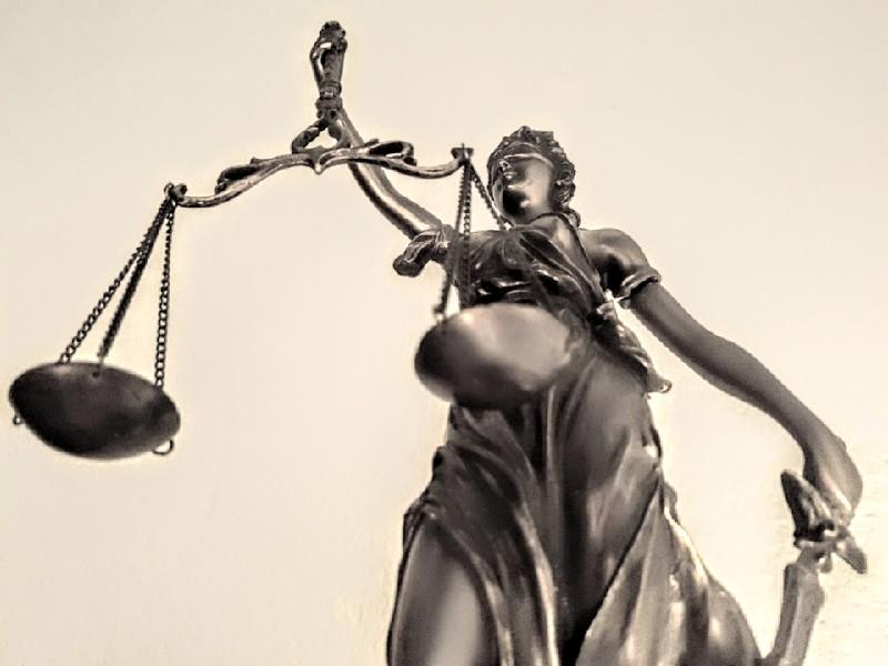 Das Foto zeigt Justitia, das Sinnbild von Recht und Gerechtigkeit, frontal von unten fotografiert erkennt man, dass sie in der rechten Hand die Waage und in der linken Hand das Schwert hält.