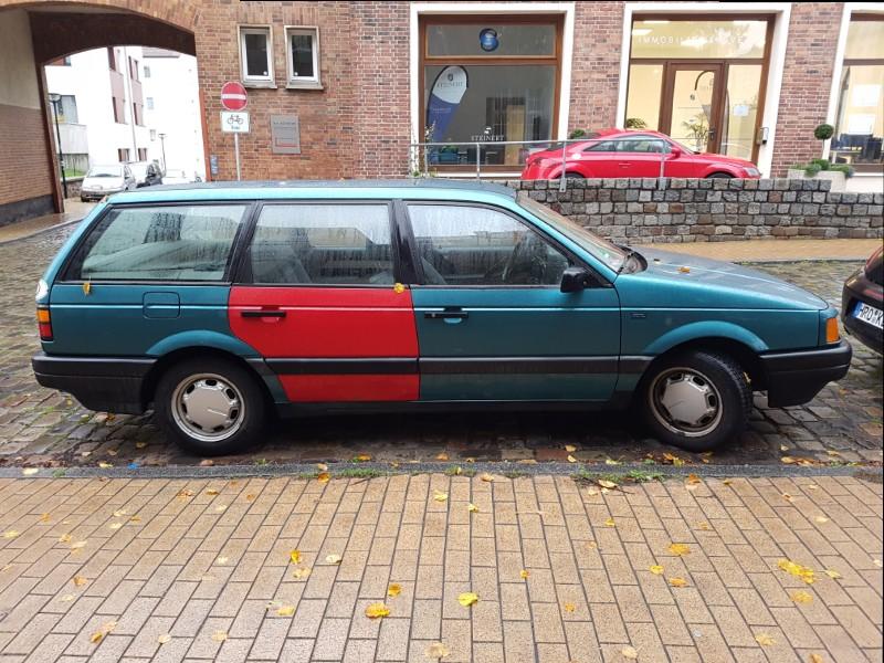 Das Foto zeigt einen älteren grünen VW Passat, bei dem eine hintere Tür rot ist.