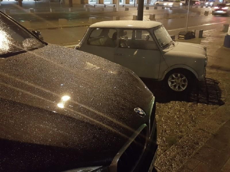 Das im Dunkeln aufgenommene Foto zeigt im Vordergrund ein großes und im Hintergrund ein kleines Auto.