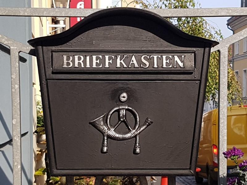 Das Foto zeigt einen dunkelgrauen Briefkasten mit der Aufschrift Briefkasten und einem stilisierten Posthorn.