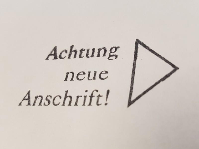 Das Foto zeigt den Stempelaufdruck mit der Angabe Achtung neue Anschrift, rechts daneben ein nach rechts weisendes Dreieck.