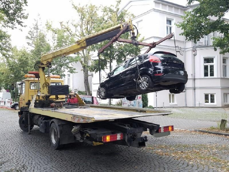 Das Foto zeigt einen Abschleppwagen, welcher einen Pkw am Haken hat.