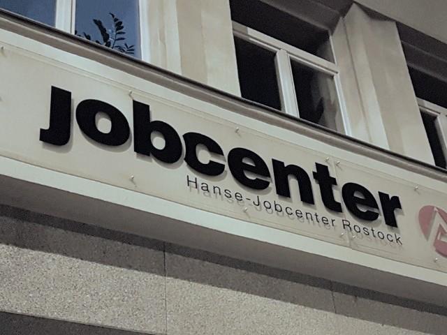 Das Foto zeigt das an einem Gebäude angebrachte Schild eines Jobcenters.