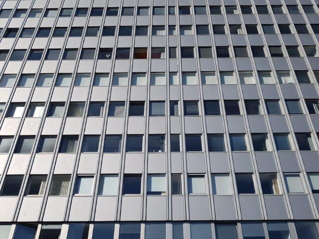 Auf dem Foto ist eine von unten fotografierte moderne Fassade zu erkennen, die hellgrau ist und zahlreiche Fenster beinhaltet.
