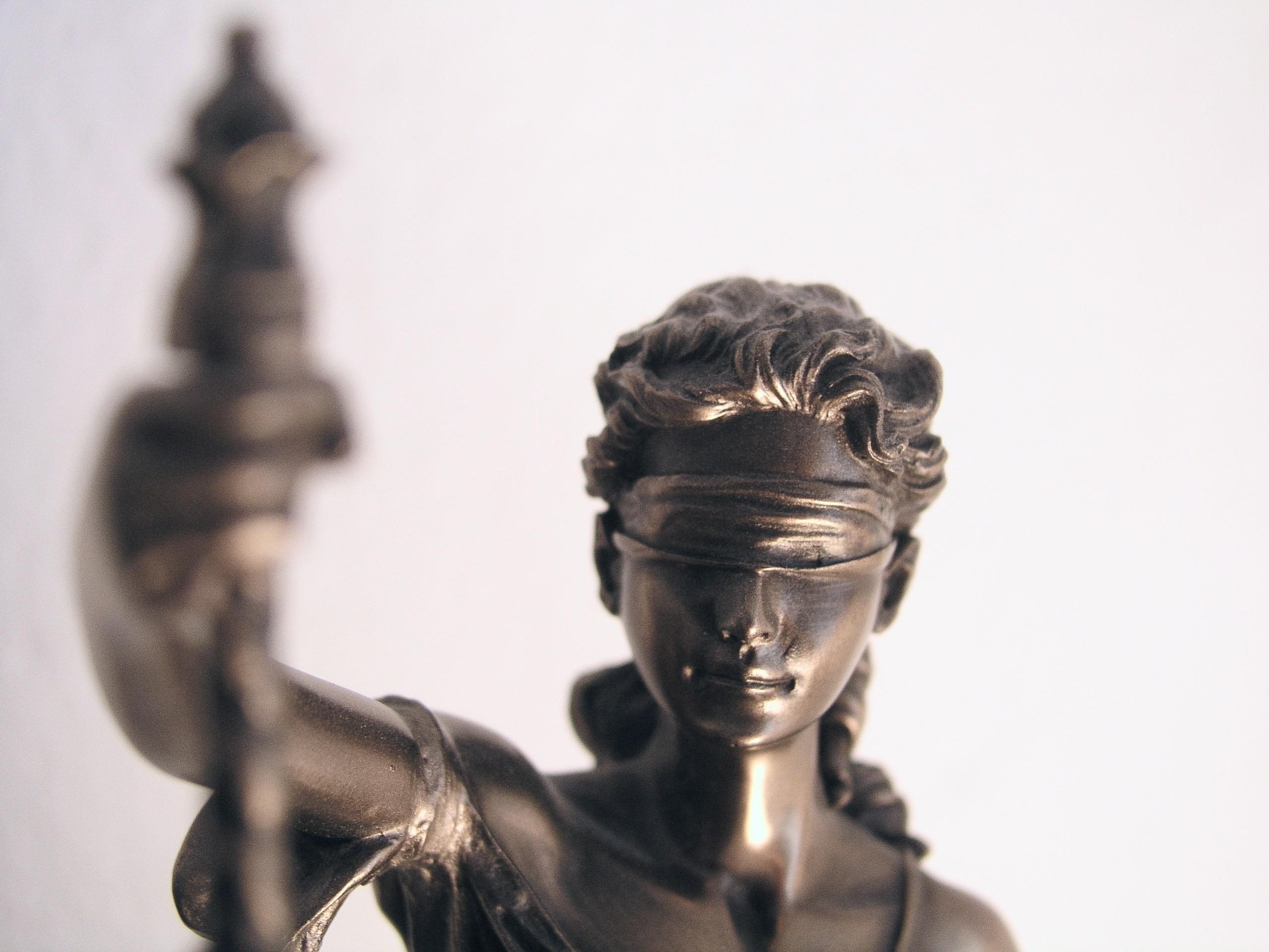Das Foto zeigt das Sinnbild von Recht und Gerechtigkeit, die Justitia. Zu sehen ist deren Kopf mit verbundenen Augen sowie im Vordergrund etwas unscharf die Hand, mit der Sie die Waage hält.