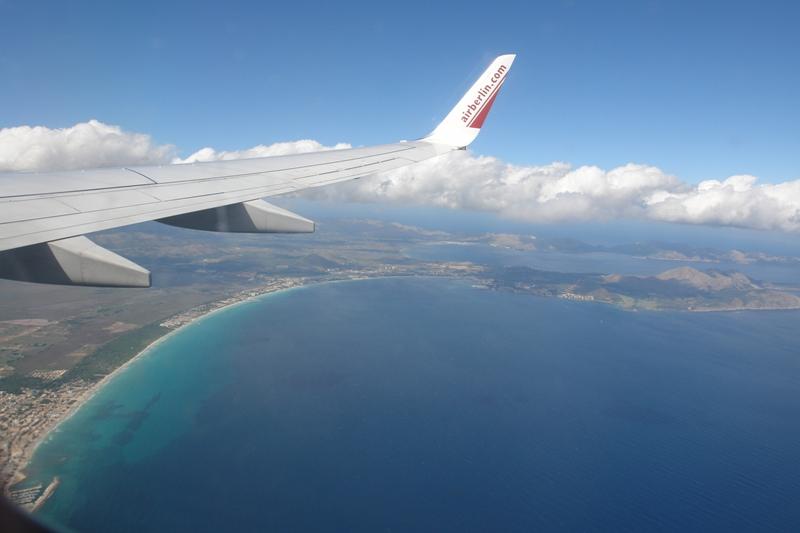 Das Foto zeigt die Aussicht aus einem fliegenden Flugzeug, zu sehen ist eine Tragfläche sowie Meer und Landfläche.