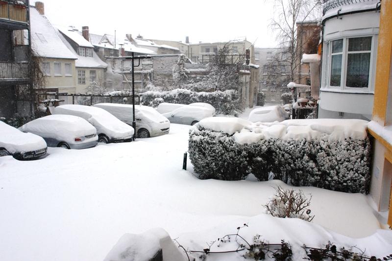 Das Foto zeigt einen verschneiten Innenhof mit schneebedeckten Autos und schneebedeckten Hecken.