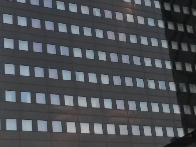 Das Foto zeigt eine dunkelgraue Fassade mit zahlreichen Fenstern, in sehr moderner Aufmachung.