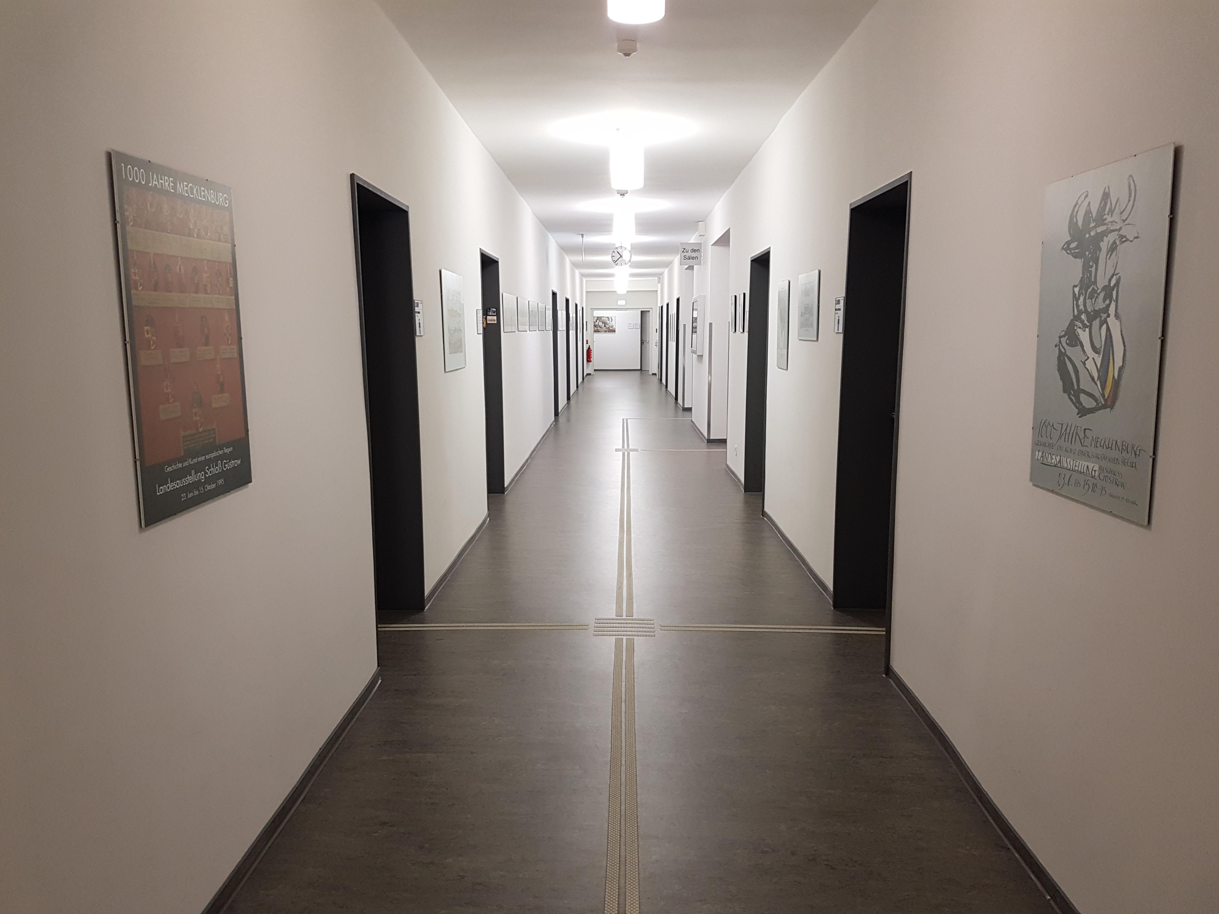 Das Foto zeigt einen Blick in einen langen Flur, von dem aus mehrere Büros abgehen.