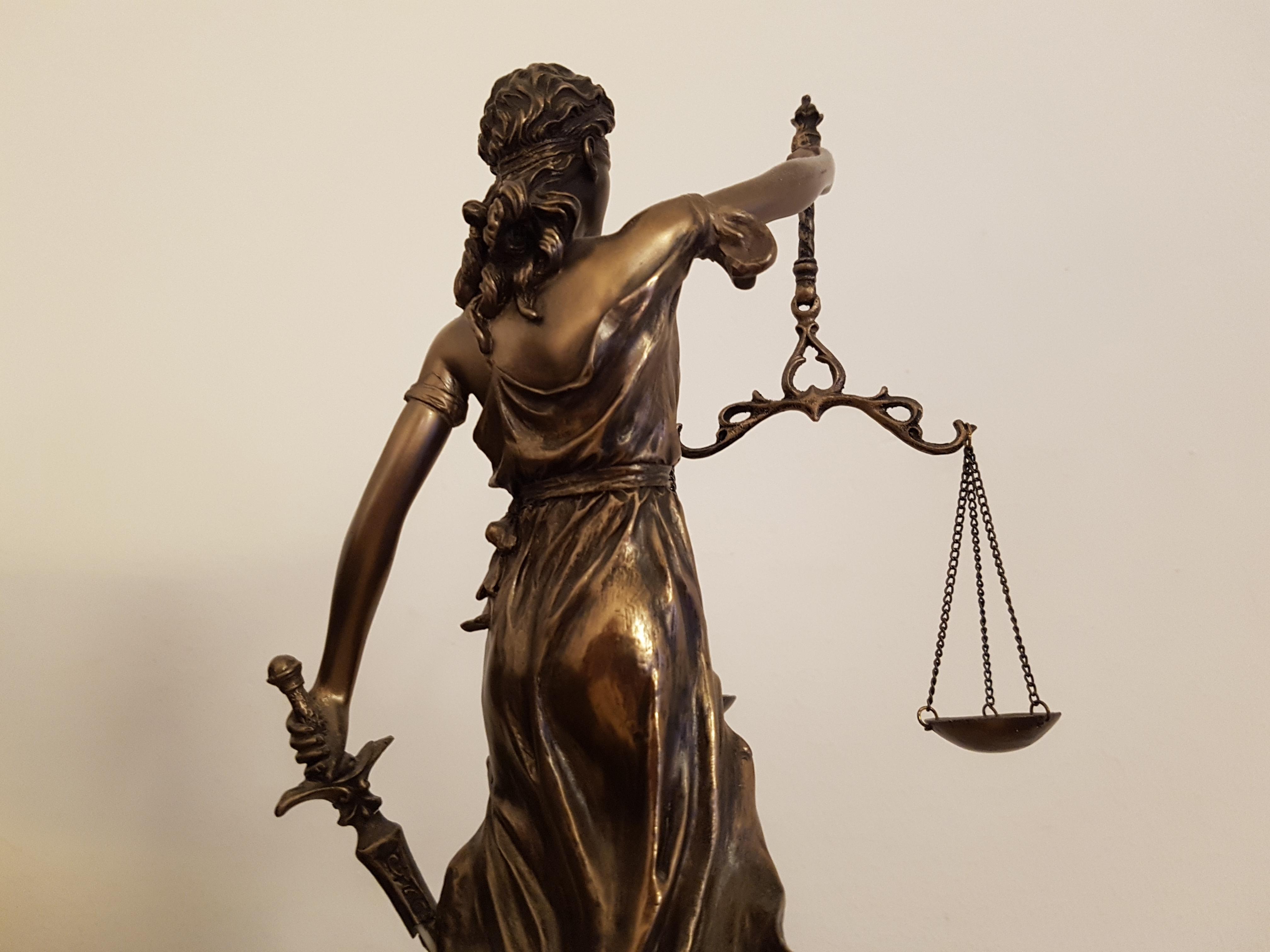 Das Foto zeigt eine von hinten fotografierte Justitia, die in der linken Hand ein Schwert und in der rechten Hand eine Waage hält.