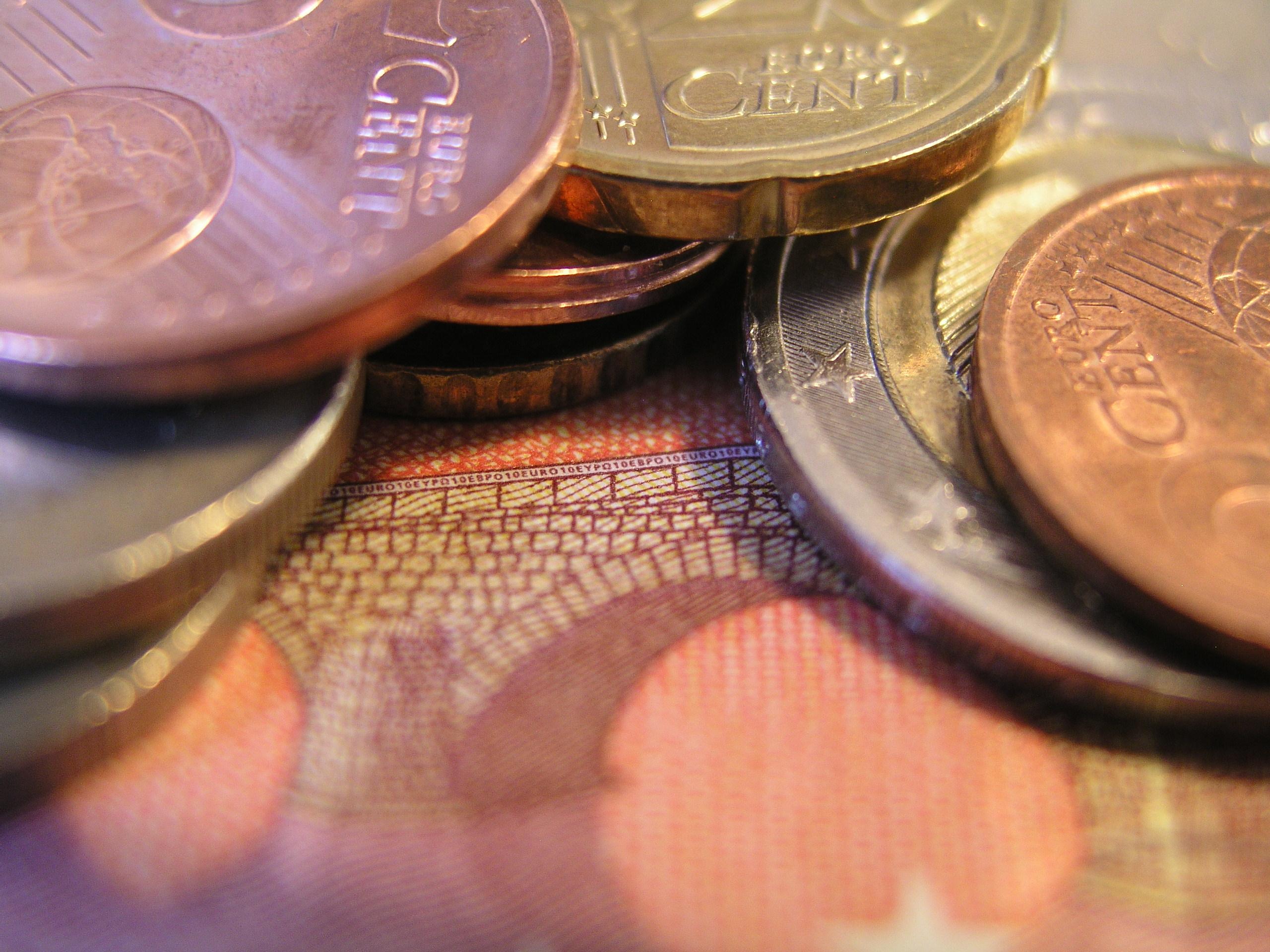 Das Foto zeigt den Ausschnitt eines 10 € Scheins, auf dem mehrere Geldmünzen liegen.